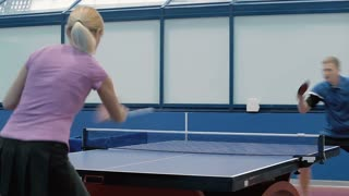 Pretty woman playing the ping-pong with young man at the court