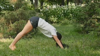 Pretty woman stretches her back and makes sport exercises in park
