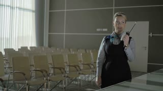 Pretty woman talks to the walkie-talkie in the conference hall