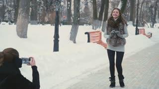 Pretty women take photo in the winter park