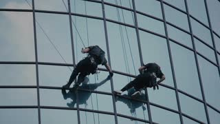 professional climbers are hanging near the windows of business center