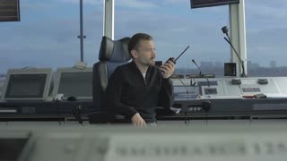 Professional dispatcher speaks with portable radio in control tower in airport