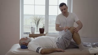 Professional masseur massages old man's knee in slowmotion