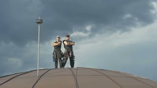 Professional steeplejacks on the roof against a cloudy sky