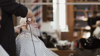 Professional stylist makes modern hairstyle to old man in barbershop