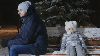 Quarrelled parents sit backs to each other with daughter on bench in winter park