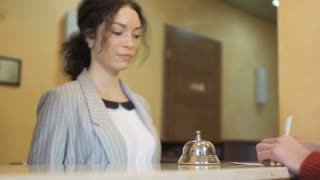Receptionist in hotel gives keys from room to guest