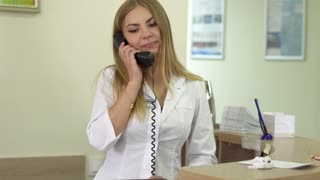 Receptionist of clinic talking by phone