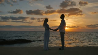 Romance couple enjoys a beautiful seascape and sunset