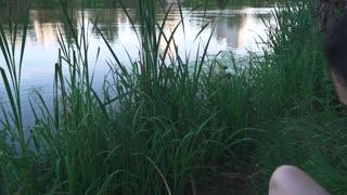 Sad girl on the river bank