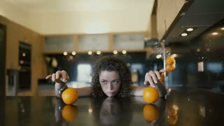 Sad girl playing with oranges on table