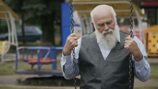 Sad old man swings on seesaw in slowmotion