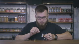 Salesman with beard complete the electronic cigarette in shop