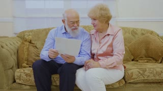Senior couple discussing the rent bills sitting on sofa in living room at home