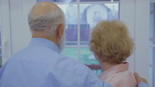 Senior couple enjoys falling snow outside the window standing at home