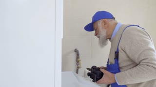 Senior gray-haired man wearing coveralls repairs boiler