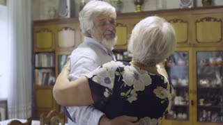 Senior man dancing with wife at home in slow motion