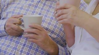 Senior man drinks tea with senior woman