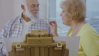 Senior man has fun with his wife drawing the picture on easel