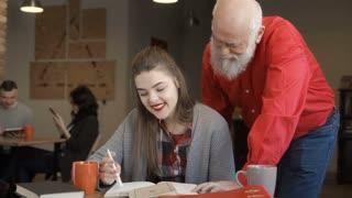 Senior man helps granddaughter to prepare to exams at university