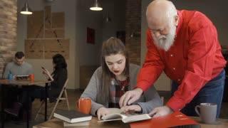 Senior man helps student to prepare to exams at university