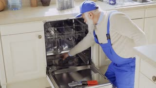 Senior man in blue overalls clean sink of the dishwasher