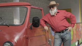 Senior man in hat and sunglasses poses near vintage car
