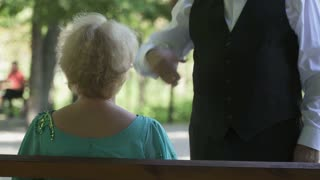 Senior man in suit invites a lady to dance a waltz