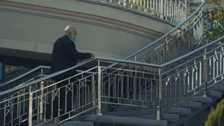 Senior man in suit walks upstairs to the urban building
