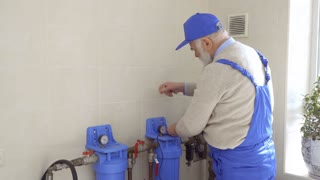 Senior man repair heating pipes in blue overalls