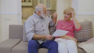 Senior man shows rent bills to his wife