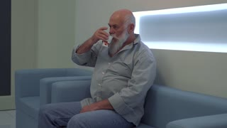 Senior man sit on sofa in clinic and wait his turn