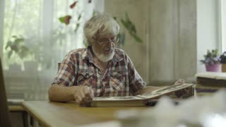 Senior man sitting at home and looking his old album with photos
