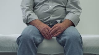 Senior man sitting on a couch in doctor's office