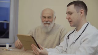 Senior man talking with doctor in clinic