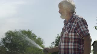 Senior man watering meadow with a water hose