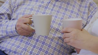 Senior woman and man drinks tea
