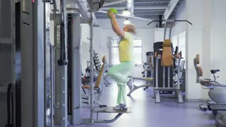 Senior woman makes exercise with ball in the gym and show thumb up