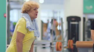 Senior woman makes exercise with barbell in the gym