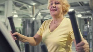 Senior woman makes exercises for legs on simulator in the gym