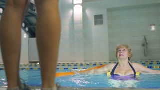 Senior woman makes exercises in swimming pool with trainer