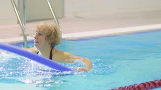 Senior woman makes exercises with noodle in pool