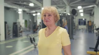 Senior woman makes healthy exercise in the gym