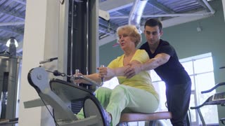 Senior woman makes pull up exercise on training apparatus in the gym