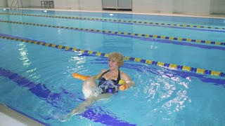 Senior woman makes sport exercises in swimming pool with noodle
