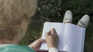 Senior woman paints inside notebook