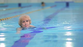 Senior woman swims in blue swimming pool