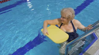 Senior woman swims in pool with special equipment