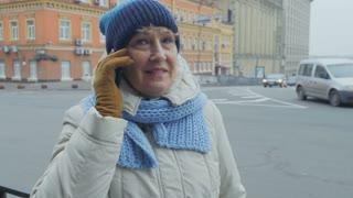 Senior woman talks on phone at the street