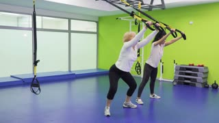 Senior woman with young brunette squats with belts in the gym